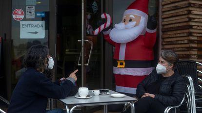 Dos personas conversan con la mascarilla puesta mientras se toman algo en la terraza de un bar, este miércoles en Ourense.
