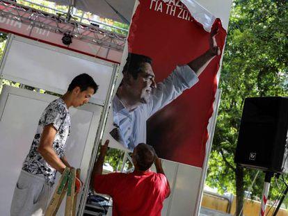 Dos operarios retiran publicidad electoral de Syriza este lunes en Atenas. En vídeo, así fue la despedida de Tsipras.