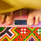 EN : A young girl monitors her weight gain. If there is no
