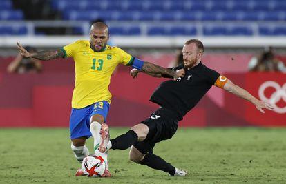 Alves trata de llevarse e balón ante Arnold.