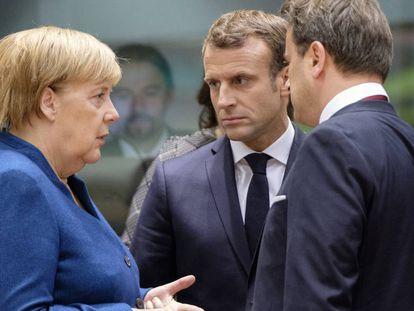 Angela Merkel habla con Emmanuel Macron y con el primer ministro de Luxemburgo, Xavier Bettel, en la cumbre europea del mes pasado.