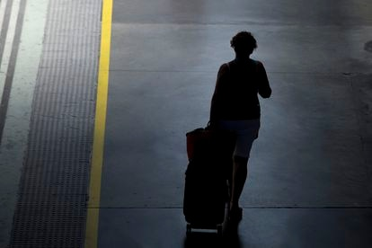 A woman drags her suitcase on a platform at the Santa Justa train station (Seville) on August 8, 2019.
