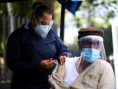 Una sanitaria vacuna a una persona contra la influenza en el marco de la campaña de vacunación contra esa enfermedad.