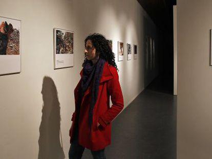 Una mujer recorre la exposición 40 Años de Acción Humanitaria Internacional en el Centre Cultural La Nau de Valencia.