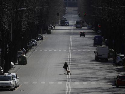 Una mujer pasea su perro por una calle de Roma, el lunes 23 de marzo.