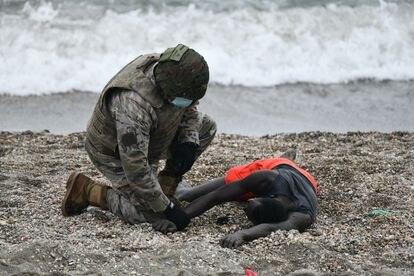 Un militar atiende a una persona tumbada en la orilla de la playa de Ceuta tras haber llegado a nado desde Marruecos, el pasado martes.