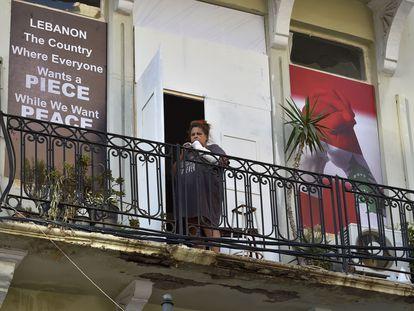 Una mujer en un balcón de una casa dañada por la explosión en el puerto de Beirut.