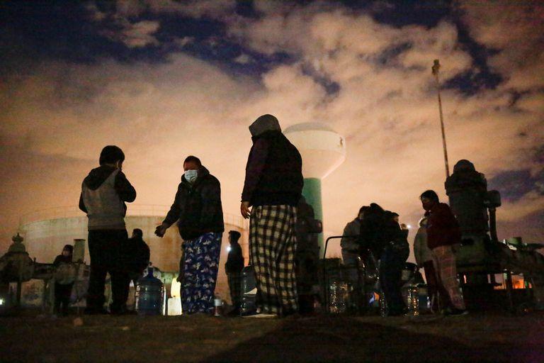 Personas llenan contenedores con agua de un tanque de almacenamiento durante el apagón de Ciudad Juárez, el 16 de febrero de 2021.