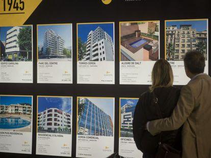 Una pareja muestra promociones inmobiliarias expuestas en el salón.