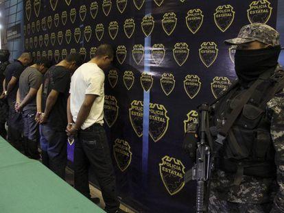 Un policía resguarda a cuatro integrantes del CJNG (imagen de archivo).