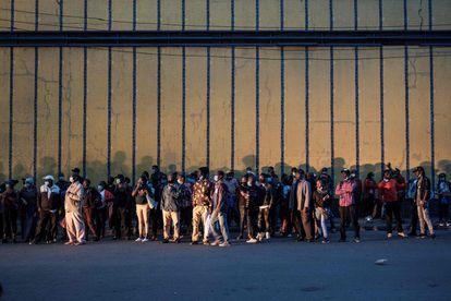 Un grupo de personas esperan un autobús para regresar a casa antes de un nuevo toque de queda de 20:00 a 4:00 en el centro de Nairobi, Kenia, el 27 de marzo de 2021.