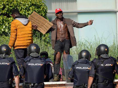 Dos temporeros protestan frente a agentes de la Policía Nacional fuera de la Institución Ferial de Albacete.