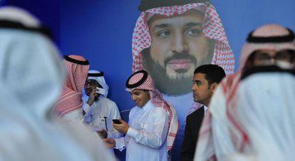 Un grupo de saudíes habla junto a un póster del príncipe heredero Mohammed bin Salman durante el Foro Misk, celebrado esta semana en Riad.