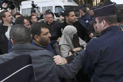La policía francesa detiene a una mujer con <i>niqab</i> durante una protesta no autorizada por el veto al velo integral en París.