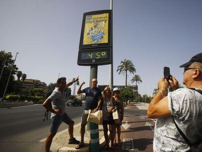 Unos turistas se fotografían debajo de un termómetro de calle que marca 45 grados, este jueves en Córdoba.