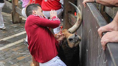 Un toro de Pedraza de Yeltes embiste a un mozo en el cuarto encierro de San Fermín 2016.