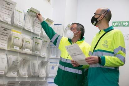 El encargado Miguel Retamal, a la izquierda, asigna una ruta de recogida de residuos a un conductor.