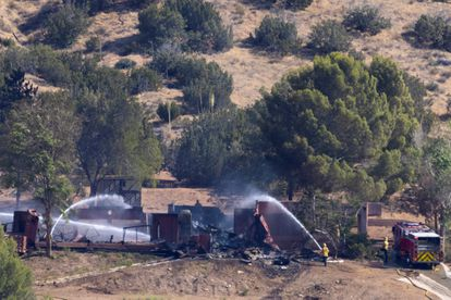 Firefighters throw water on the remains of the property of the alleged murderer of Agua Dulce.