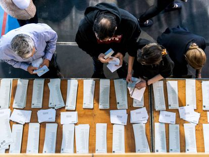 Electores en mesa de papeletas y sobres en un colegio electoral.