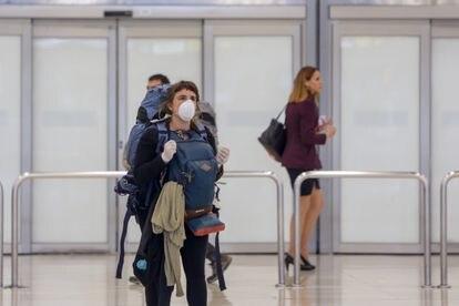 Una mujer protegida con mascarilla en la Terminal 4 del Aeropuerto Adolfo Suárez-Madrid Barajas el 24 de marzo.