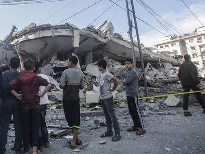 Palestinos inspeccionan los escombros tras un ataque aéreo israelí en una zona residencial de la franja de Gaza este martes 13 de noviembre.