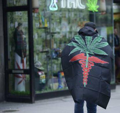 Un activista junto a una tienda que vende marihuana en Canadá.