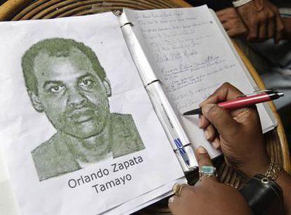 Una mujer firma en el libro de condolencias por Orlando Zapata.