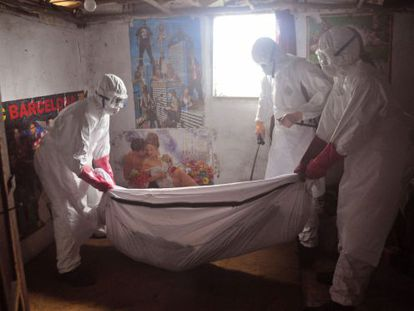 Trabajadores sanitarios retiran el cadáver de un muerto de ébola en una casa de las afueras de Monrovia (Liberia).