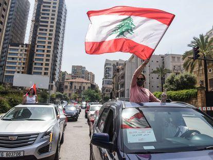 Una manifestante ondea la bandera libanesa durante un convoy de protesta durante la sesión parlamentaria este martes en Beirut