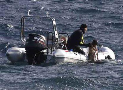 Los servicios de Emergencias rescatan a uno de los cadáveres de la patera que volcó anoche en Lanzarote