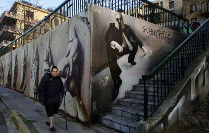Una mujer, junto una pintada que representa un hombre de negocios con un casco de espartanos, en el centro de Atenas.
