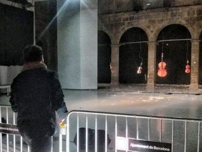 Un visitante lanza piedras a los instrumentos musicales en la instalación de Cabosanroque en Ars Santa Mònica.