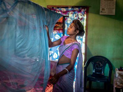 Una mujer coloca una mosquitera en su casa en Assam, India.