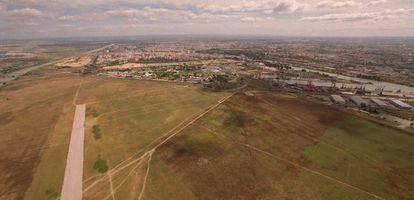 Vista aérea de los terrenos de Tablada con Sevilla al fondo.
