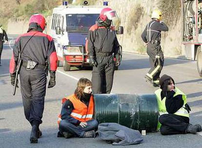 Dos jóvenes cortan una de las entradas principales a Bilbao encadenados a un bidón de cemento.