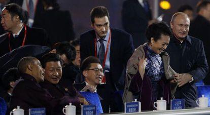 El presidente ruso, Vladímir Putin, ayuda a ponerse una manta sobre los hombros a Peng Liyuan, mujer de su homólogo chino Xi Jinping, sentado junto a Barack Obama. Pekín ha tratado de censurar el vídeo con la escena.
