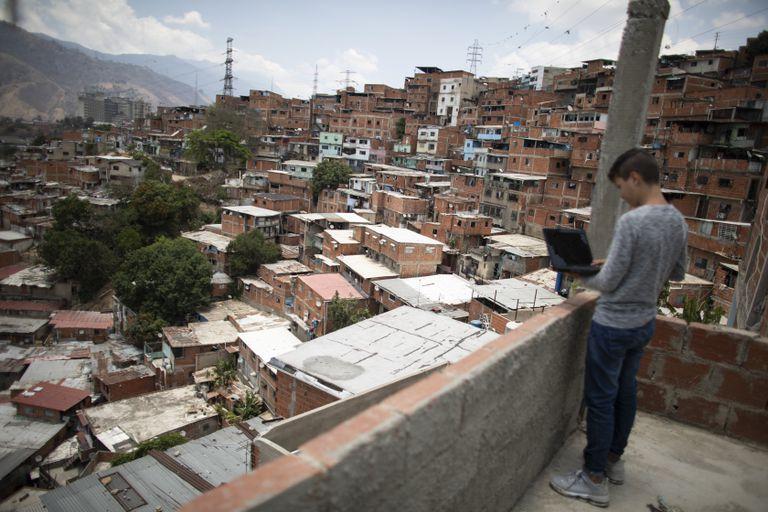 Un estudiante adolescente intenta conectarse a internet desde la azotea de su casa en Caracas, Venezuela, el 7 de mayo.