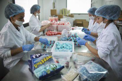 Varias mujeres confeccionan paquetes de productos Wonkandy en la planta sevillana de la empresa