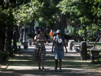 Varias personas caminan por el Paseo del Prado, en Madrid.
