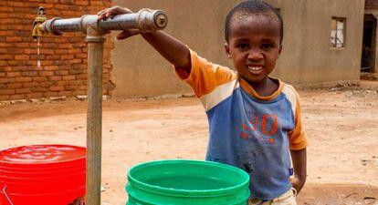 Un niño posa junto al punto de agua potable de su pueblo, Kihurio, en Tanzania.