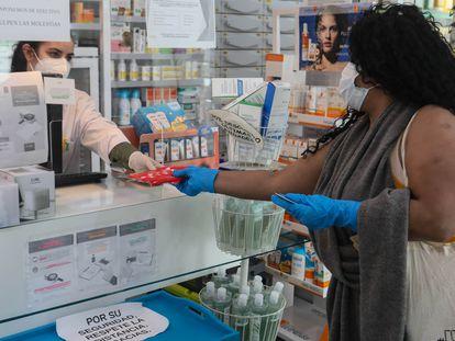 Un farmacéutico entrega a un cliente una de las mascarillas en una farmacia de Madrid.