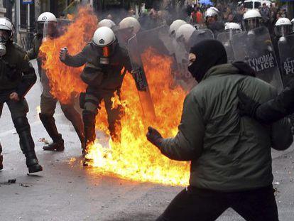 Manifestantes se enfrentan con policías antidisturbios durante una protesta con motivo de la huelga general en Atenas
