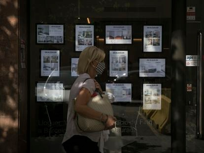 Una mujer pasa ante el escaparate de una inmobiliaria en Barcelona, el mes pasado.