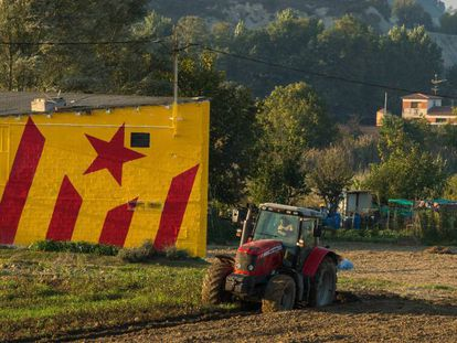 Un agricultor con un tractor ante una fachada que tiene pintada una 'estelada'