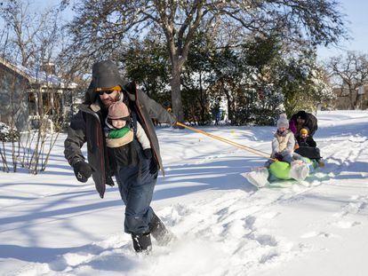 Un hombre arrastra a sus hijas en un trineo plástico en Austin, Texas.