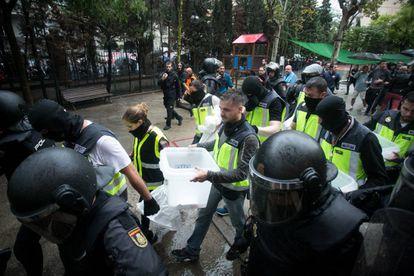 Agentes de la Policia Nacional intervienen las urnas en el colegio Ramon Llull.