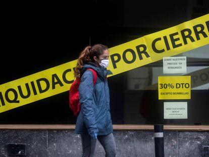 Un mujer pasa, este lunes, frente a una tienda en fase de liquidación en Córdoba.