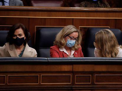 La ministra de Asuntos Económicos, Nadia Calviño (c), conversa con la ministra de Trabajo, Yolanda Díaz, junto a la vicepresidenta primera, Carmen Calvo, en el Congreso, la pasada semana.