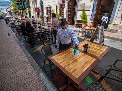 Una empleada de un restaurante limpia una mesa, la semana pasada en el centro de Bogotá.