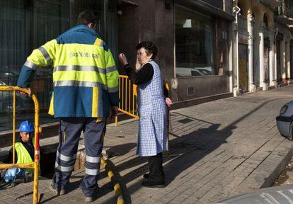 Una vecina del Poblenou, Rosalía, inquiere a un operario sobre la marcha de los trabajos de reparación.